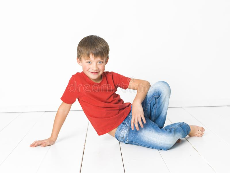 Netter und blonder Junge mit rotem Hemd und Blue Jeans wirft auf weißem Bretterboden auf lizenzfreies stockfoto