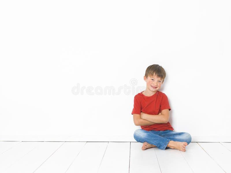 Netter und blonder Junge mit rotem Hemd und Blue Jeans wirft auf weißem Bretterboden auf lizenzfreies stockbild
