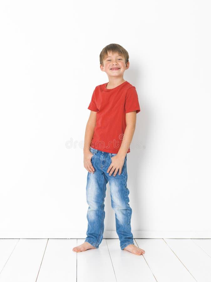 Netter und blonder Junge mit rotem Hemd und Blue Jeans wirft auf weißem Bretterboden auf stockbilder