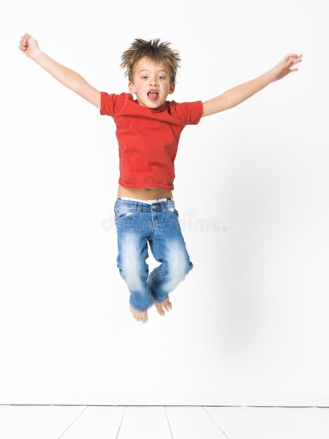 Netter und blonder Junge mit rotem Hemd und Blue Jeans wirft auf weißem Bretterboden auf stockbild