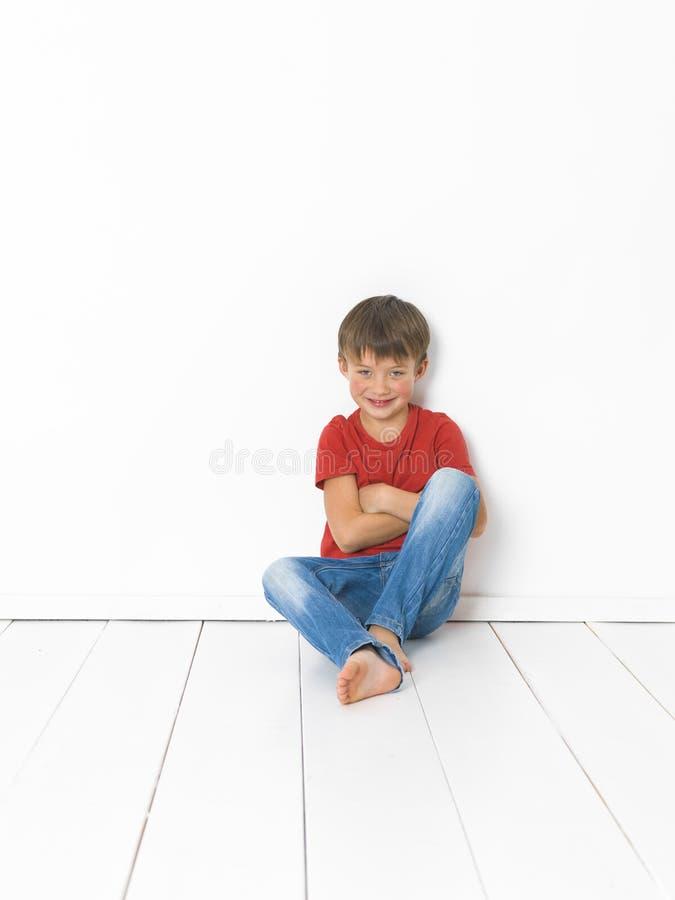 Netter und blonder Junge mit rotem Hemd und Blue Jeans wirft auf weißem Bretterboden auf stockfoto