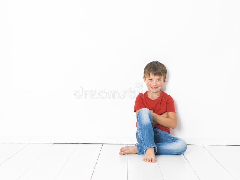 Netter und blonder Junge mit rotem Hemd und Blue Jeans wirft auf weißem Bretterboden auf lizenzfreie stockfotos