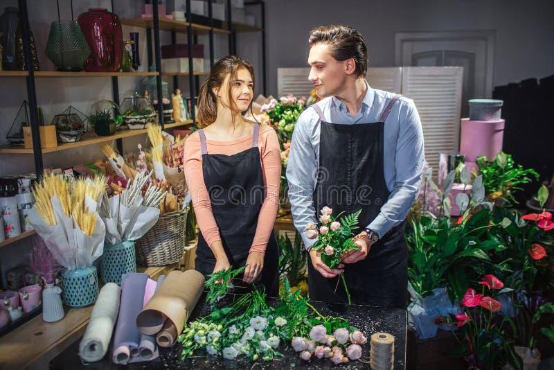Netter und netter junger Mann und Frau betrachten einander Sie machen Blumensträuße bei Tisch Leute sind glücklich Sie stehen her lizenzfreie stockfotografie