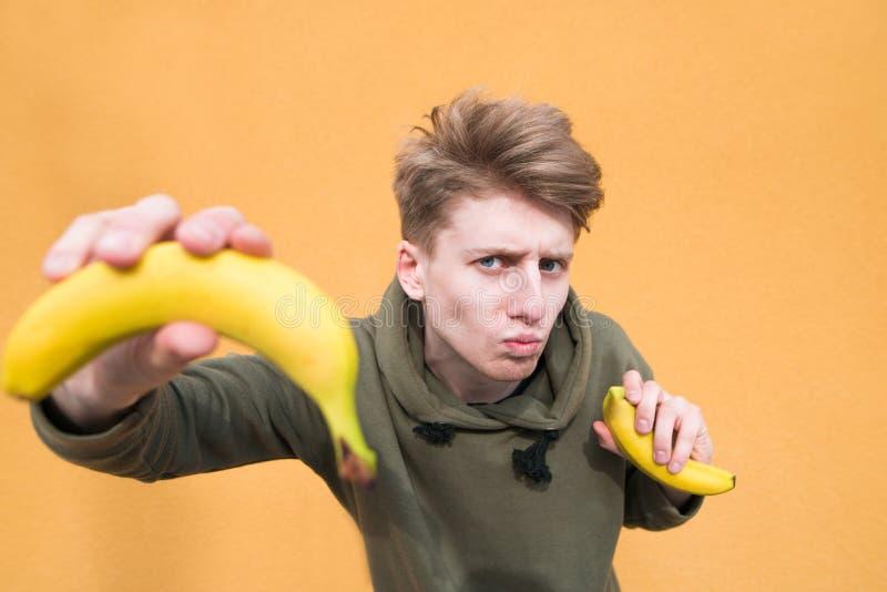 Netter und lustiger junger Mann mit Bananen in seinen Händen, die auf einem orange Hintergrund mit Bananen in seinen Händen aufwe lizenzfreie stockfotografie