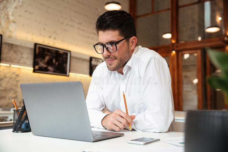 Netter unrasierter Geschäftsmann im weißen Hemd, das Laptop s betrachtet stockbild