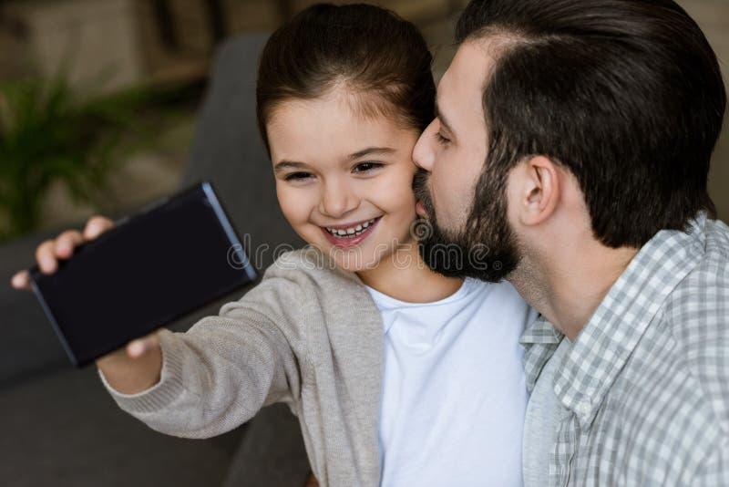 netter Vater mit der Tochter, die selfie auf Smartphone nimmt lizenzfreie stockbilder