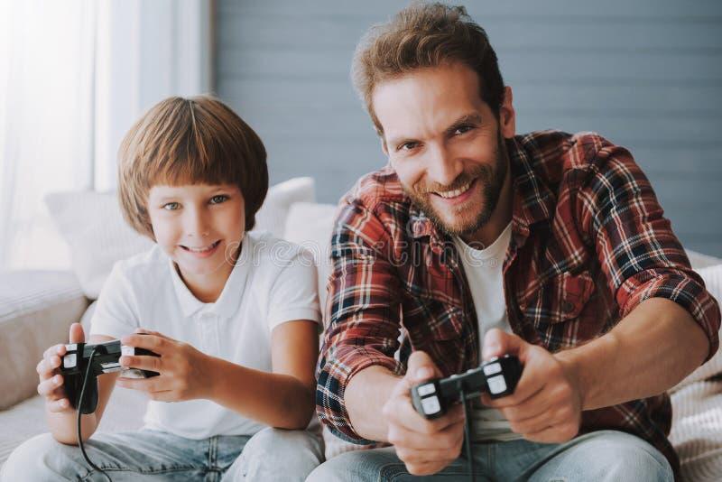 Netter Vater mit Gamecontroller spielt Videospiel mit dem kleinen Sohn, der auf Couch sitzt stockfotos