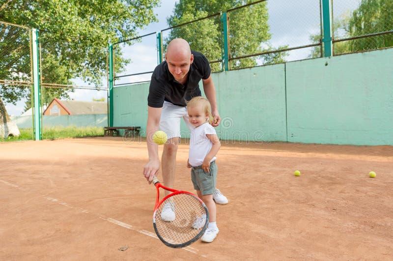 Netter Vater und nette kleine Tochter spielen am Tennisplatz stockfoto