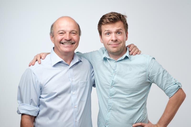 Netter Vater und Sohn, die zusammen umarmt und aufwirft stockfotografie