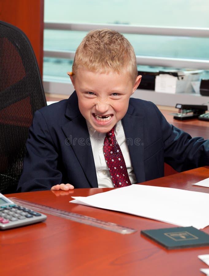 Netter verärgerter Junge im Büro stockfotografie