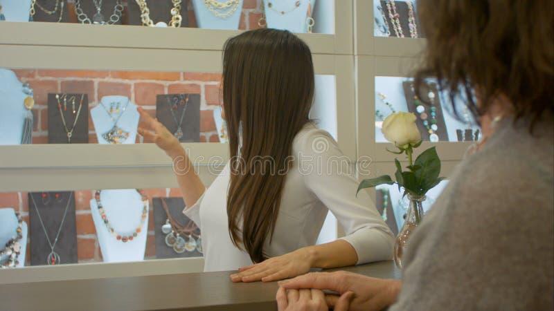 Netter Verkäuferberater bietet an, etwas Schmuck zu einem Kunden in einem Juweliergeschäft zu wählen stockfotografie