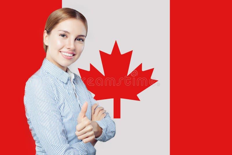Netter Vertretungsdaumen der jungen Frau oben gegen die Kanada-Flagge lizenzfreie stockfotografie