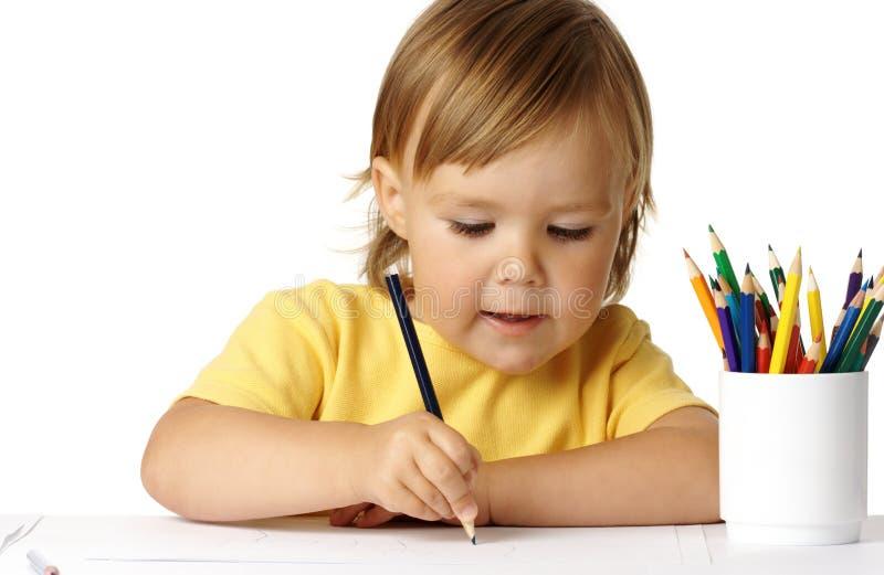 Netter Vorschüler gerichtet auf ihre Zeichnung stockfotos