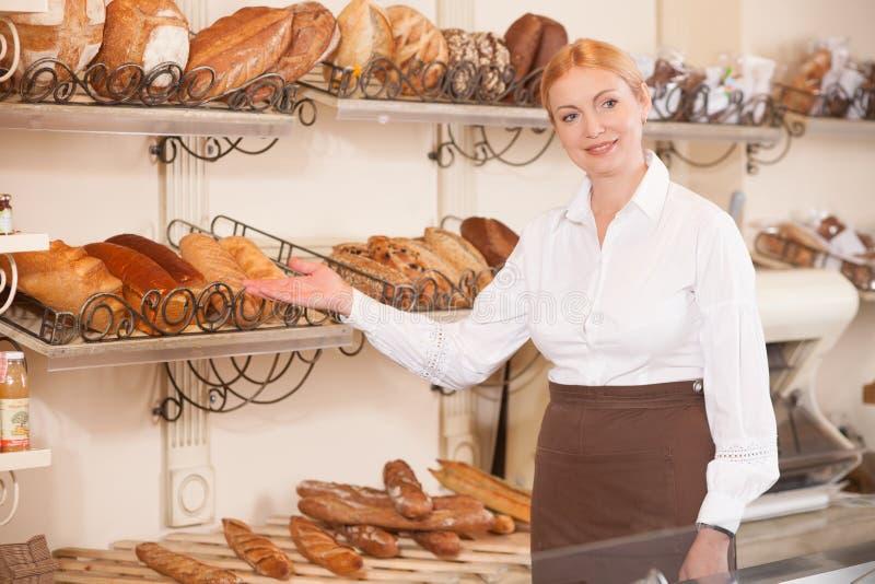 Netter weiblicher Bäcker lädt zu ihrem Shop ein stockfotografie