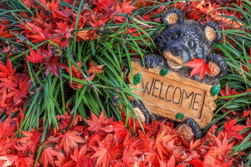 Netter willkommener Bär - umgeben von buntem Autumn Leaves lizenzfreies stockbild
