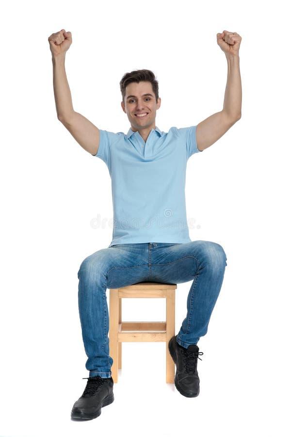 Netter zufälliger Mann, der mit seinen Händen in der Luft feiert stockfotografie