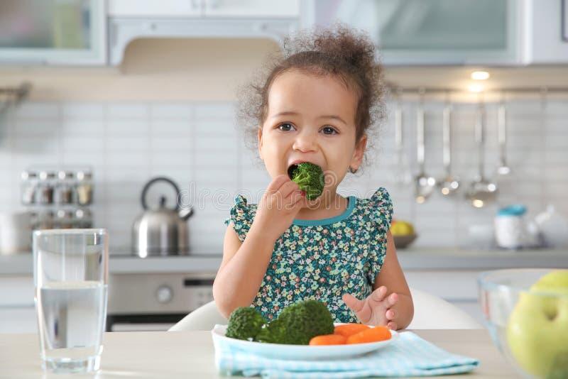 Nettes afro-amerikanisches Mädchen, das bei Tisch Gemüse isst stockfoto