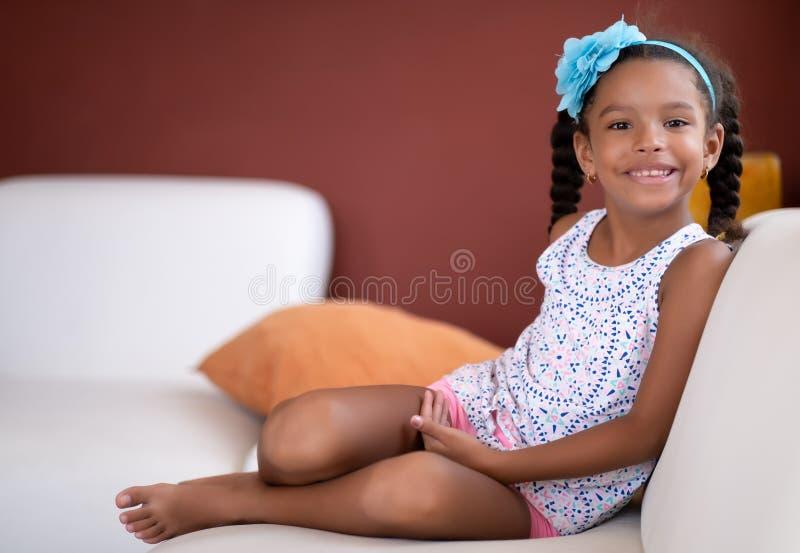 Nettes Afroamerikanermädchen, das auf einer Couch und einem Lächeln sitzt stockfoto