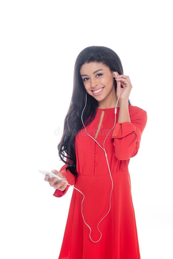 nettes Afroamerikanermädchen in rotes Kleiderhörender Musik in den Kopfhörern mit dem Smartphone lokalisiert lizenzfreie stockfotografie