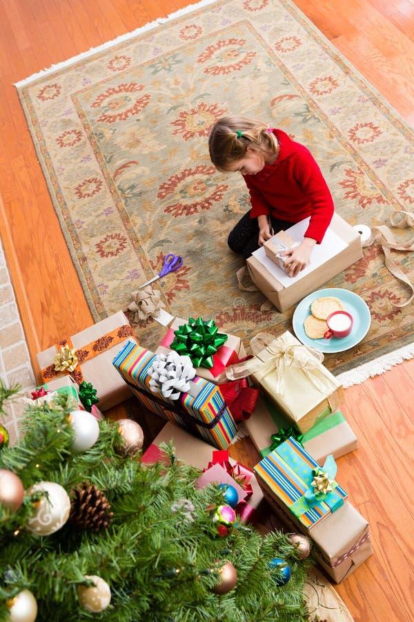 Nettes altes Fünfjahresmädchen, das ein Weihnachtsgeschenk einwickelt lizenzfreies stockfoto