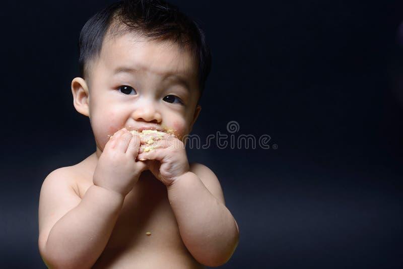 Nettes asiatisches Baby isst Kuchen mit beiden seine Hand lizenzfreies stockfoto