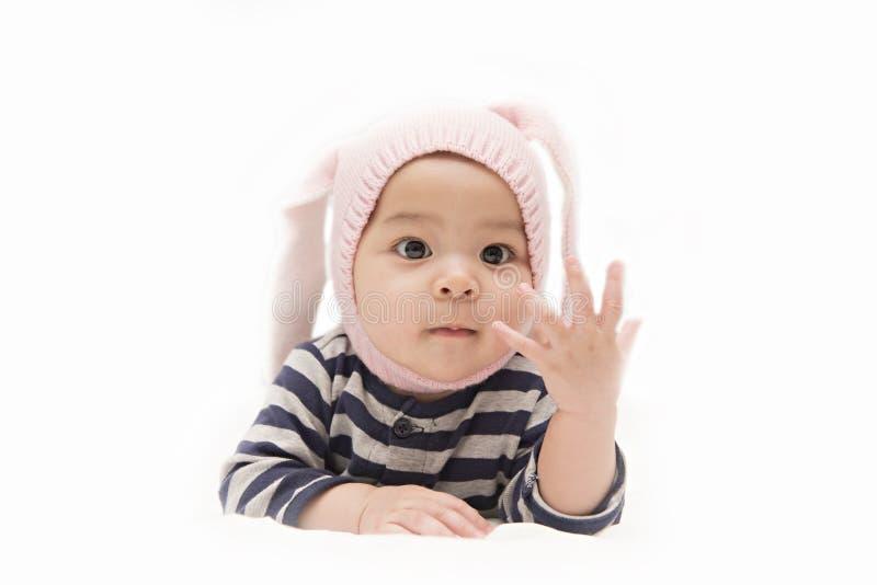 Nettes asiatisches Baby mit dem Kaninchenhut, der ihre Finger auf weißem Hintergrund zeigt lizenzfreie stockfotos