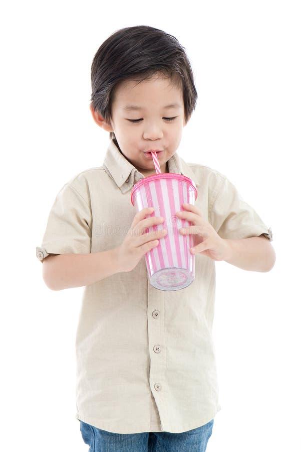 Nettes asiatisches Kind, das mit Papierstroh trinkt stockfoto