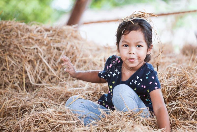 Nettes asiatisches Kindermädchen, das den Spaß, zum mit Heustapel zu spielen hat lizenzfreie stockfotografie