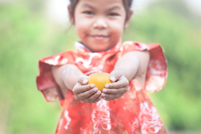 Nettes asiatisches Kindermädchen, das eine Orange hält lizenzfreie stockfotografie