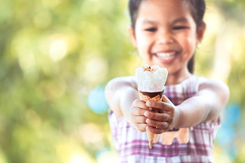 Nettes asiatisches kleines Kindermädchen, das köstlichen Eiscremekegel hält lizenzfreie stockfotos