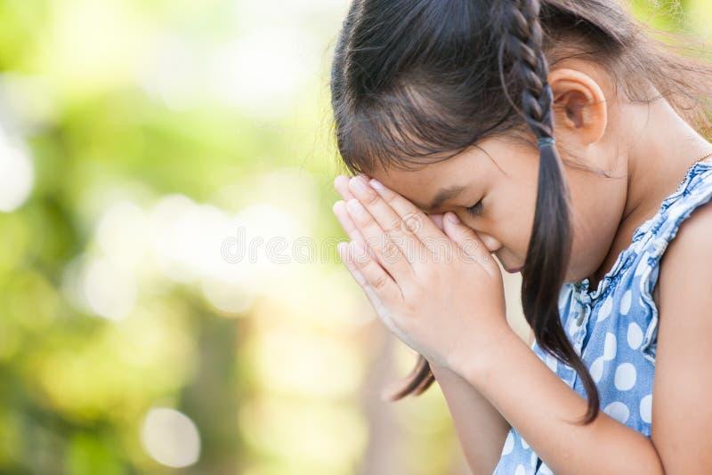 Nettes asiatisches kleines Kindermädchen, das mit gefaltet ihrer Hand betet stockfotos