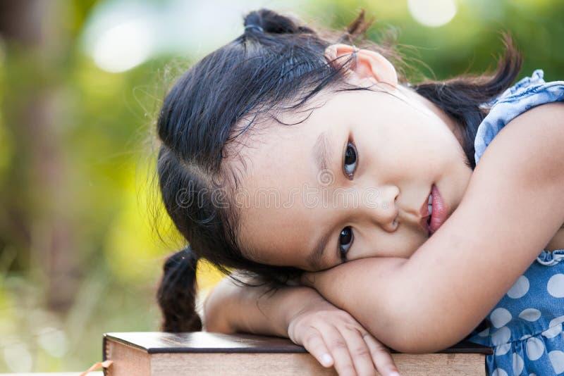Nettes asiatisches kleines Kindermädchen mit dem gebohrten Gefühl, zum eines Buches zu lesen stockfoto