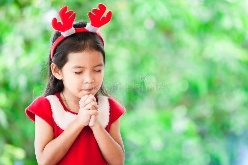 Nettes asiatisches kleines Mädchen im Weihnachtskleid schloss ihre Augen stockfoto