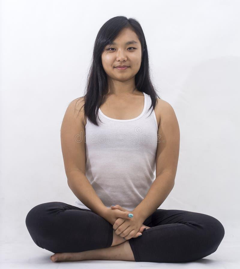 Nettes asiatisches Mädchen auf lokalisiertem Hintergrund meditierend lizenzfreies stockbild