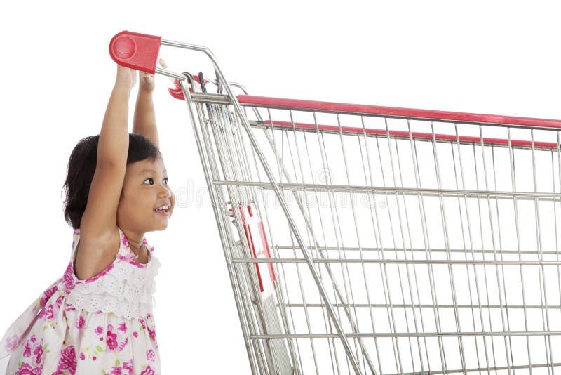 Nettes asiatisches Mädchen, das Laufkatze drückt lizenzfreies stockfoto