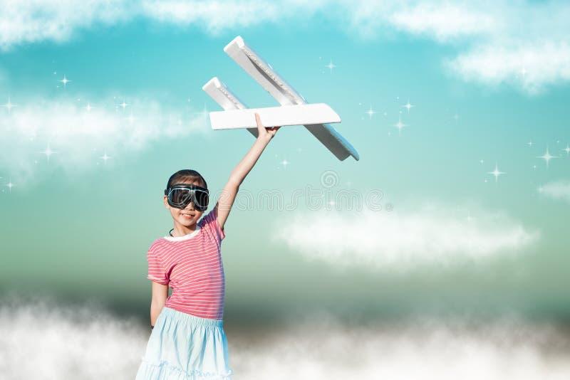 Nettes asiatisches Mädchen, das Spielzeugflugzeug als Versuchsphantasie zum fu spielt lizenzfreies stockbild