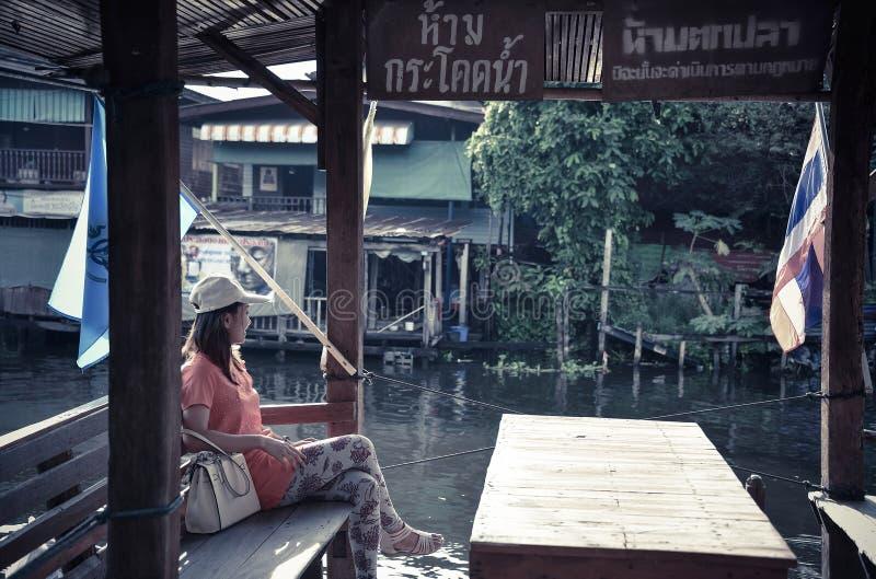 Nettes asiatisches thailändisches Mädchen ist im Pavillon nahe er Flussufer entspannend lizenzfreie stockfotos