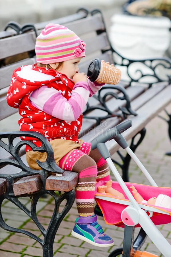 Nettes Baby auf dem Weg mit Spielzeugspaziergänger stockbilder