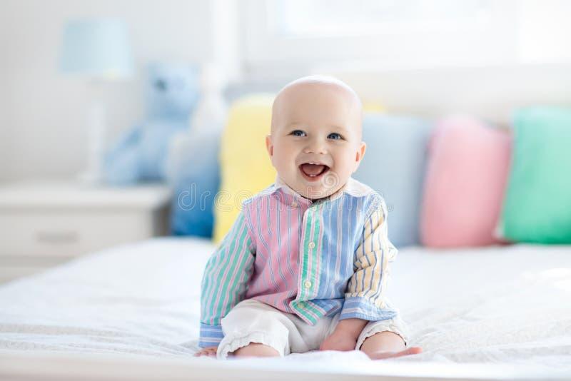 Nettes Baby auf weißem Bett stockfoto
