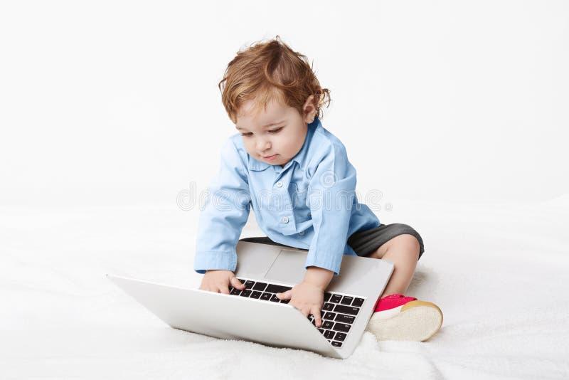 Nettes Baby, das auf Laptoptastatur schreibt lizenzfreie stockbilder