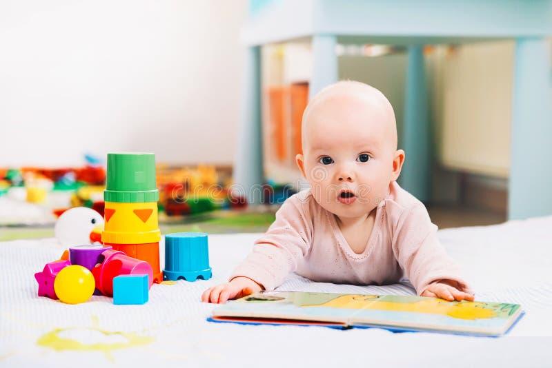 Nettes Baby, das ein Buch schaut und liest stockfoto