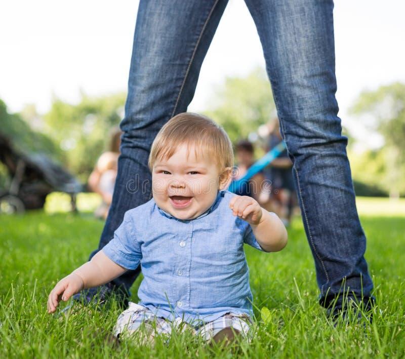 Nettes Baby, das in Front Of Mother In Park sitzt lizenzfreie stockfotografie