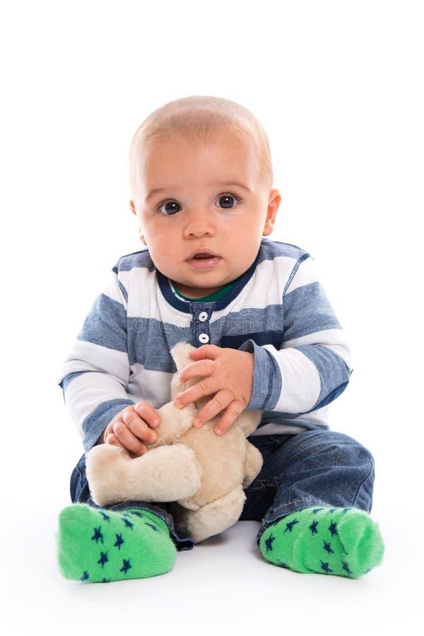 Nettes Baby, das im gestreiften haltenen SpitzenTeddybären lokalisiert auf Weiß sitzt stockfotos