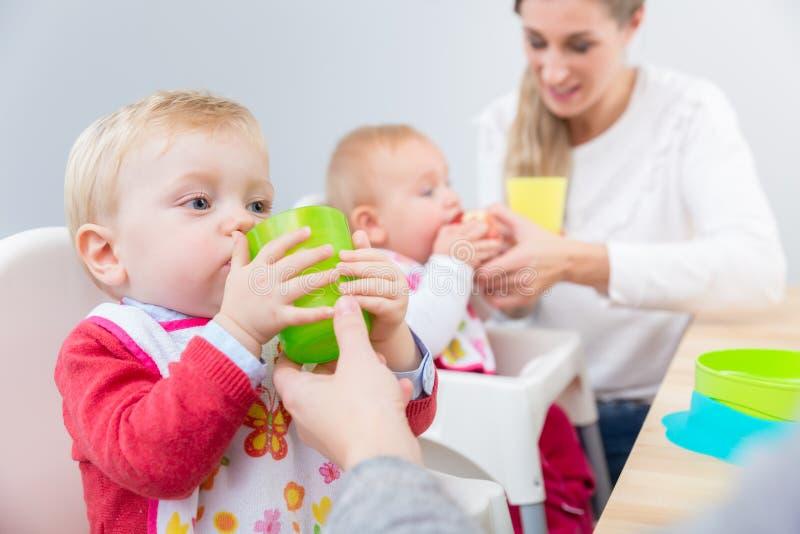 Nettes Baby, das lernt, Wasser von einem Plastikglas zu trinken stockbild