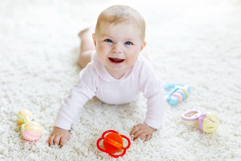Nettes Baby, das mit buntem Pastellweinlesegeklapperspielzeug spielt Neugeborenes Kind, kleines Mädchen, welche die Kamera betrac lizenzfreie stockbilder