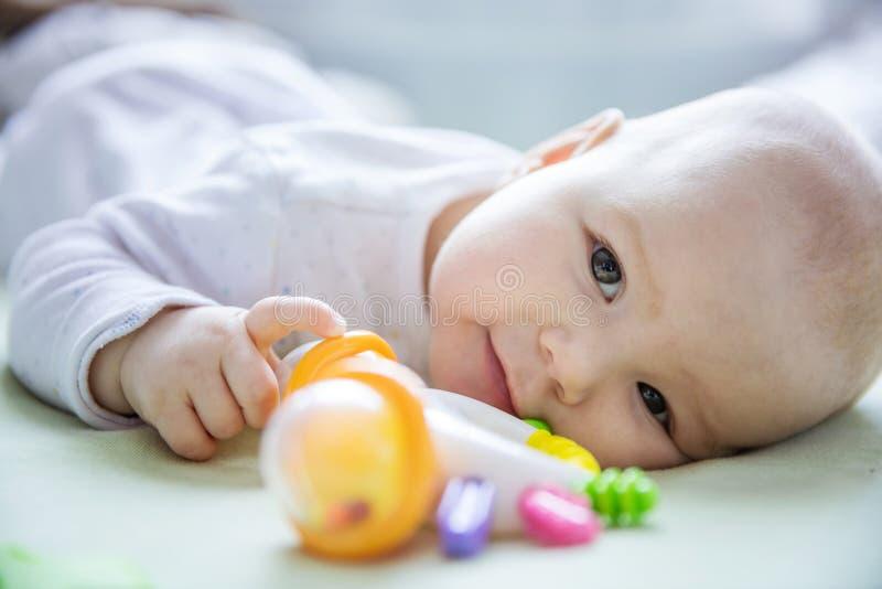 Nettes Baby, das mit Geklapper beim auf Bett zu Hause sich hinlegen spielt lizenzfreie stockfotos