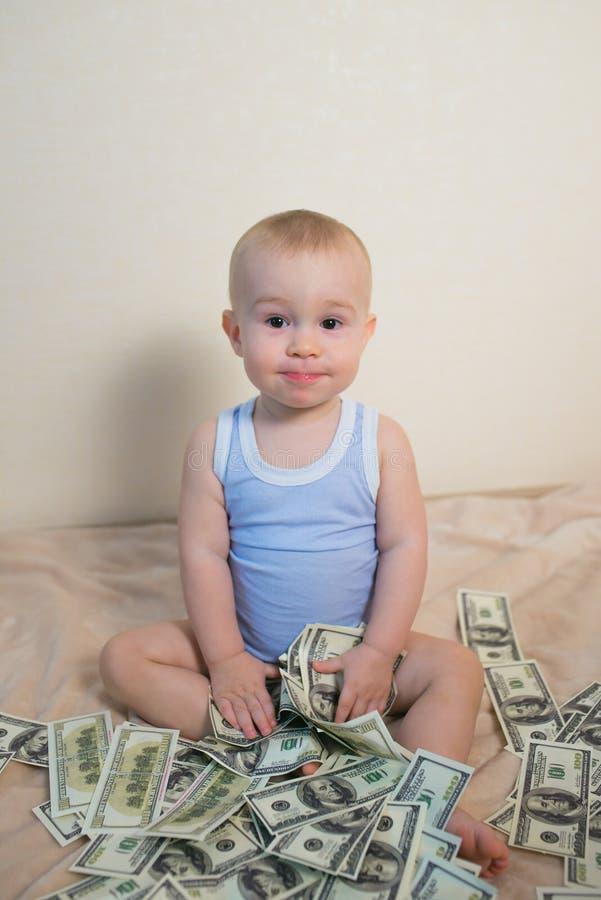 Nettes Baby, das mit Geld, hundreeds von Dollar spielt stockfotografie