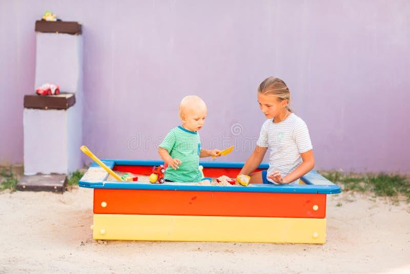 Nettes Baby, das mit seiner Schwester im Sandkasten spielt stockfotos