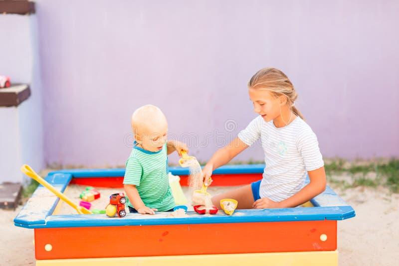Nettes Baby, das mit seiner Schwester im Sandkasten spielt lizenzfreies stockfoto