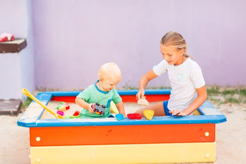 Nettes Baby, das mit seiner Schwester im Sandkasten spielt stockfotografie